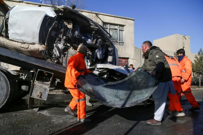 Municipal workers clean up debris at the site of a bomb attack in Kabul on December 22, 2020, where civilians have long paid a disproportionate price in the war