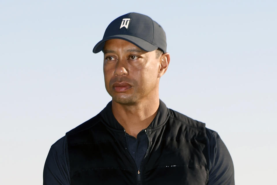 """FILE - Tiger Woods looks on during the trophy ceremony on the practice green after the final round of the Genesis Invitational golf tournament at Riviera Country Club, Sunday, Feb. 21, 2021, in the Pacific Palisades area of Los Angeles. Woods was injured Tuesday, Feb. 23, 2021, in a vehicle rollover in Los Angeles County and had to be extricated from the vehicle with the """"jaws of life"""" tools, the Los Angeles County Sheriff's Department said.(AP Photo/Ryan Kang)"""
