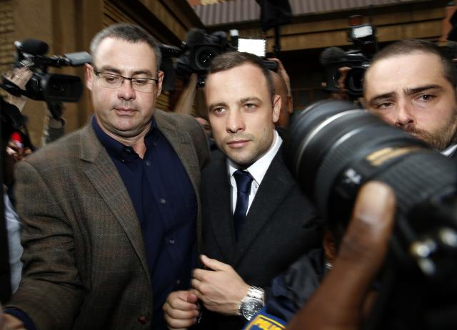 Members of the media photograph Olympic and Paralympic track star Oscar Pistorius (C) as he leaves after his trial at the North Gauteng High Court in Pretoria March 4, 2014. Pistorius is on trial for murdering his girlfriend Reeva Steenkamp at his suburban Pretoria home on Valentine's Day last year. He says he mistook her for an intruder. REUTERS/Siphiwe Sibeko (SOUTH AFRICA - Tags: CRIME LAW MEDIA SPORT ATHLETICS)