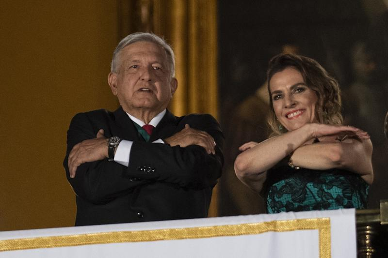 "Mexican President Andres Manuel Lopez Obrador and his wife Beatriz Gutierrez Muller gesture from the main balcony of the National Palace during the ceremony ""The Shout"" (El Grito) marking the start of Independence Day celebrations in Mexico City on September 15, 2019. (Photo by PEDRO PARDO / AFP) (Photo credit should read PEDRO PARDO/AFP/Getty Images)"
