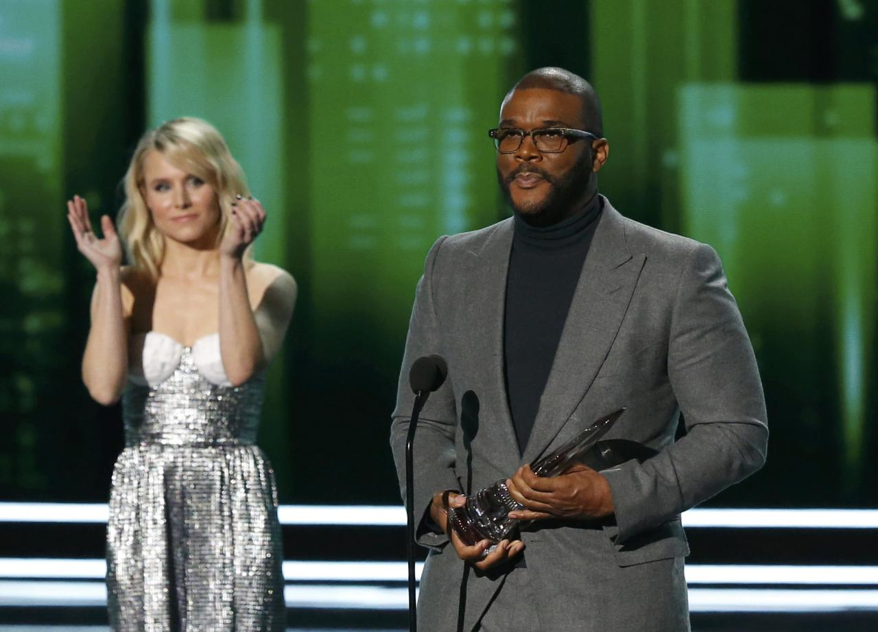 Director Tyler Perry accepts the Favorite Humanitarian Award as presenter Kristen Bell applauds at the People's Choice Awards 2017 in Los Angeles, California, U.S., January 18, 2017.  REUTERS/Mario Anzuoni