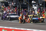 FILE - Kyle Busch, right, and Denny Hamlin make pit stops during the NASCAR Cup Series auto race Sunday, Nov. 10, 2019, in Avondale, Ariz. There is no sport that offers the same access to its stars or the action teams can and do give spots on their pit stand to honorary guests ranging from friends, family or corporate partners and its a critical cog in how NASCAR does business and what draws people to the races.(AP Photo/Ralph Freso, File)