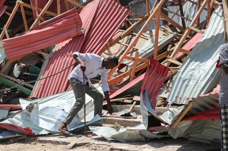 A Mogadishu resident tries to scavenge items from his damaged home after car bomb explosion (AFP Photo/Abdirazak Hussein FARAH)