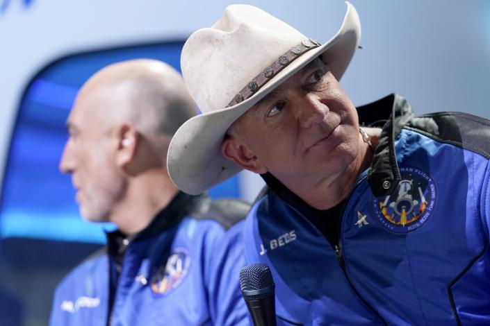 Mark Bezos, left, and Jeff Bezos, right, founder of Amazon and space tourism company Blue Origin, watch a video playback of their flight experience from the spaceport near Van Horn, Texas, Tuesday, July 20, 2021. (AP Photo/Tony Gutierrez)