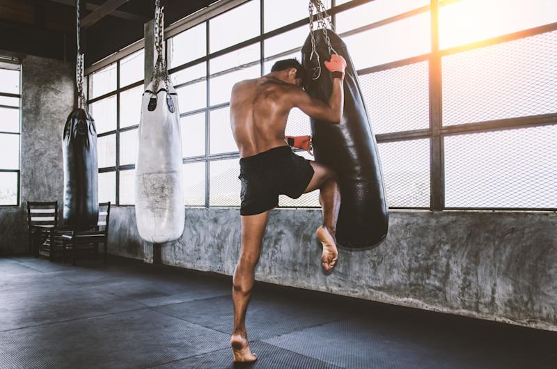 Muay thai fighter training in the gym with the punch bag