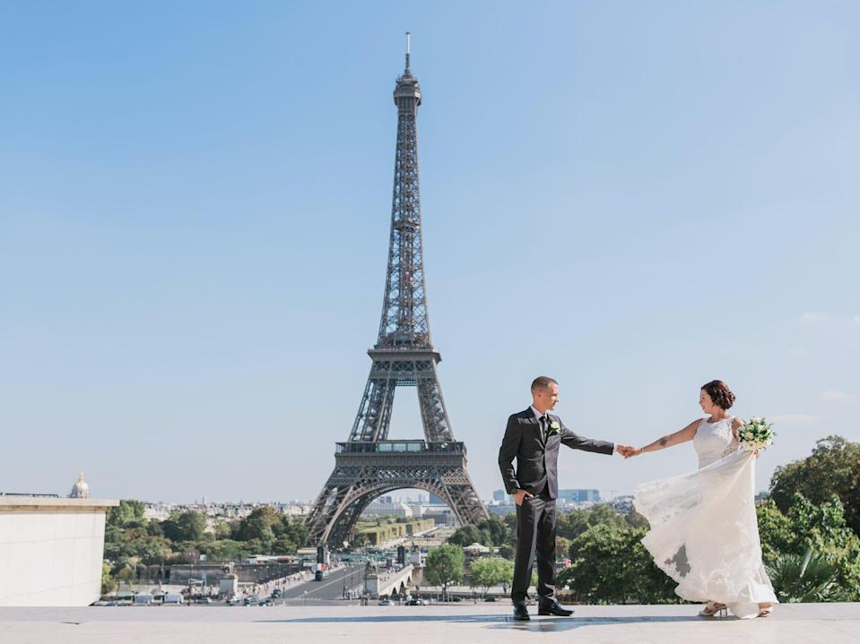 A bride and groom hold hands and look at each other with the Eiffel Tower behind them.