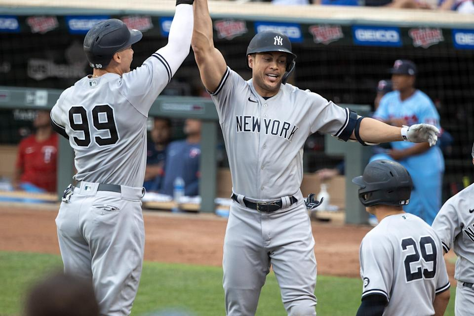 Giancarlo Stanton celebrates with Aaron Judge after hitting a three-run home run against the Twins.