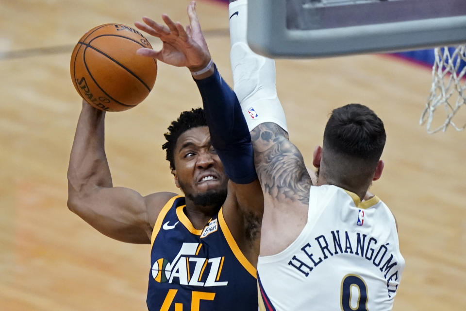 Utah Jazz guard Donovan Mitchell (45) shoots against New Orleans Pelicans center Willy Hernangomez in the second half of an NBA basketball game in New Orleans, Monday, March 1, 2021. (AP Photo/Gerald Herbert)