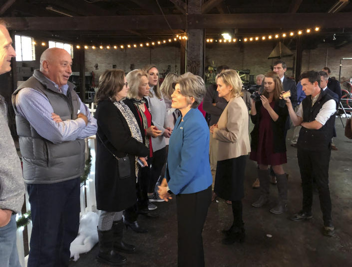 Sen. Cindy-Hyde Smith, right, R-Miss., and Sen. Joni Ernst, front center, R-Iowa, greet supporters attending a Hyde-Smith campaign event Sunday, Nov. 25, 2018, at the Mississippi Industrial Heritage Museum in Meridian, Miss. Hyde-Smith, appointed by Mississippi Gov. Phil Bryant, faces Democrat Mike Espy in a runoff election Tuesday for the remaining two years of a Senate term begun by Thad Cochran before he retired. (AP Photo/Jeff Amy)