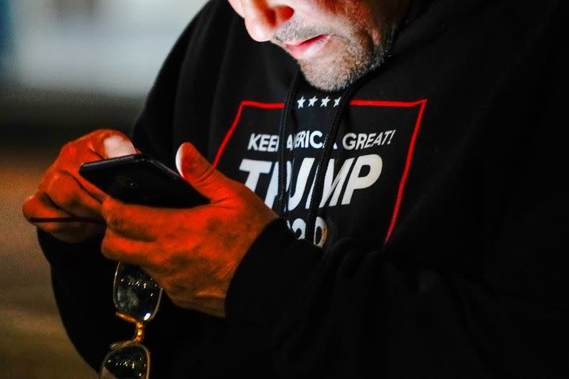 "A man wearing a ""Trump 2020"" sweatshirt uses his mobile phone during a ""Stop the Steal"" protest outside Milwaukee Central Count the day after Milwaukee County finished counting absentee ballots, in Milwaukee"