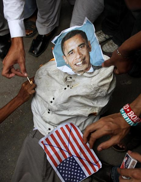 Supporters of a Insaf Student Federation burn an effigy of U.S. President Barack Obama and a representation of a U.S. flag demonstration in Karachi, Pakistan on Saturday, Sept. 15, 2012 as part of widespread anger across the Muslim world about a film ridiculing Islam's Prophet Muhammad. (AP Photo/Fareed Khan)