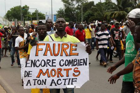 """A man holds up a sign, which reads: """"Faure still how many death by you"""", during an opposition protest calling for the immediate resignation of President Faure Gnassingbe in Lome, Togo, September 6, 2017. REUTERS/Noel Kokou Tadegnon"""