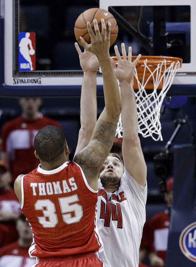Houston forward TaShawn Thomas (35) shoots over the reach of Louisville forward Stephan Van Treese (44) during the first half of an NCAA college basketball game in the semifinals of the American Athletic Conference men's tournament Friday, March 14, 2014, in Memphis, Tenn. (AP Photo/Mark Humphrey)