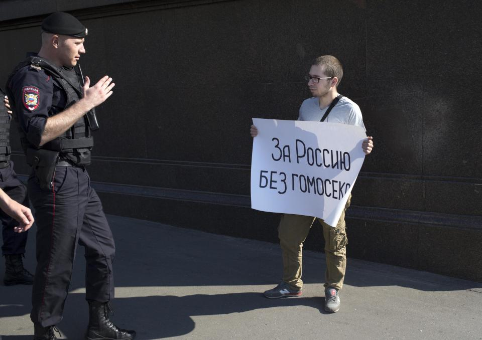 "A police officer speaks with a demonstrator near the State Duma, Russia's lower parliament chamber, in Moscow Tuesday, June 11, 2013. A controversial bill banning ""homosexual propaganda"" is expected to be approved by Russia's lower house of parliament for the second and third of three hearings on Tuesday. Poster reads: ""For Russia without homosexuals."" (AP Photo/Alexander Zemlianichenko)"