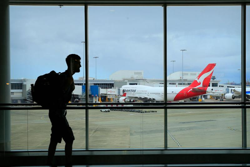 A passenger walks past a Qantas jet at the International terminal at Sydney Airport.