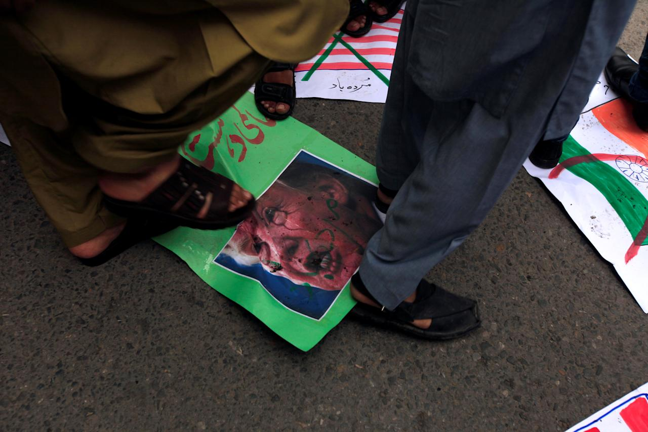 Supporters of religious and political party Jamaat-e-Islami (JI) step over the image of U.S. President Donald Trump, during a protest against the U.S. decision of putting the leader of an anti-India militant group Syed Salahuddin on its list of global terrorists, in Rawalpindi, Pakistan June 28, 2017.   REUTERS/Faisal Mahmood