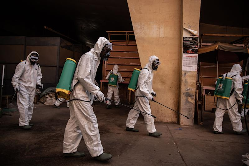 Workers dressed in full body gear disinfects the Rood Woko great market