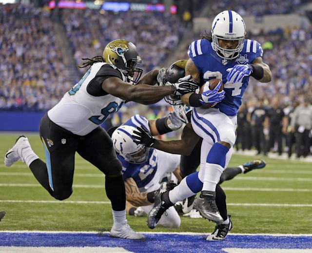 Indianapolis Colts' Trent Richardson (34) runs past Jacksonville Jaguars' Sen'Derrick Marks (99) for a 2-yard touchdown run in the first half of an NFL football game Sunday, Dec. 29, 2013, in Indianapolis. (AP Photo/Michael Conroy)