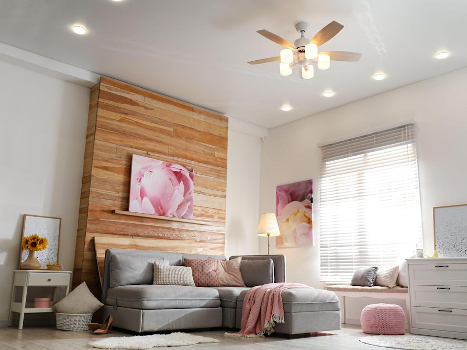 Stylish living room interior with modern ceiling fan and comfortable couch