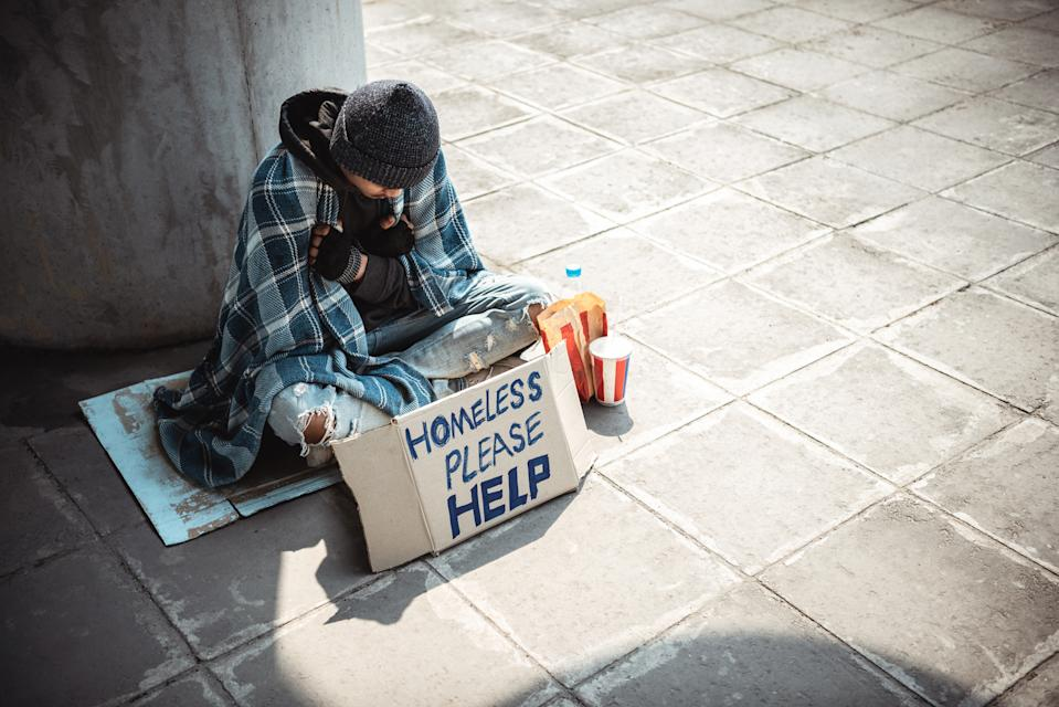 One man, young homeless sitting on the street and begging.