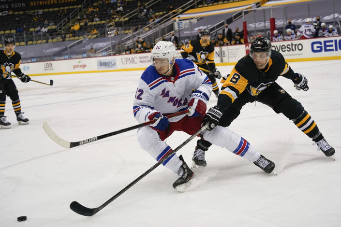 New York Rangers' Julien Gauthier (12) and Pittsburgh Penguins' Brian Dumoulin (8) chase the puck during the second period of an NHL hockey game, Sunday, March 7, 2021, in Pittsburgh. (AP Photo/Keith Srakocic)