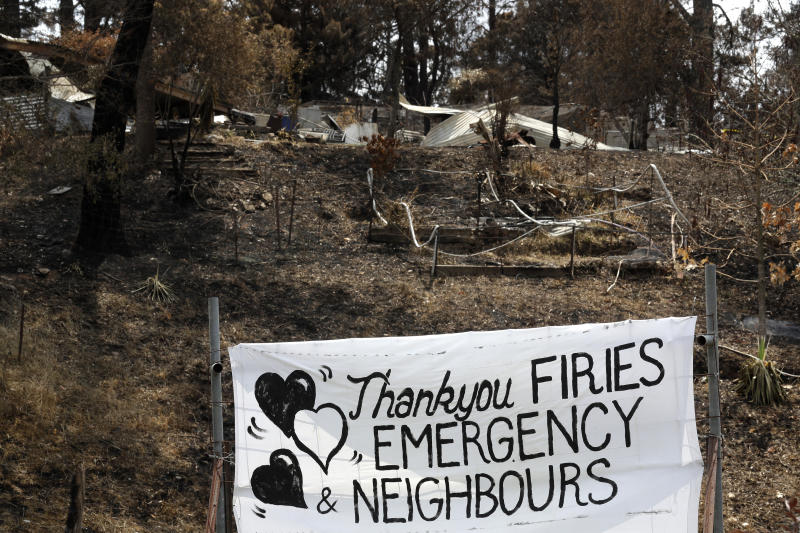 "A makeshift banner in front of the charred remains of a structure says, ""thankyou firies emergency neighbours""."