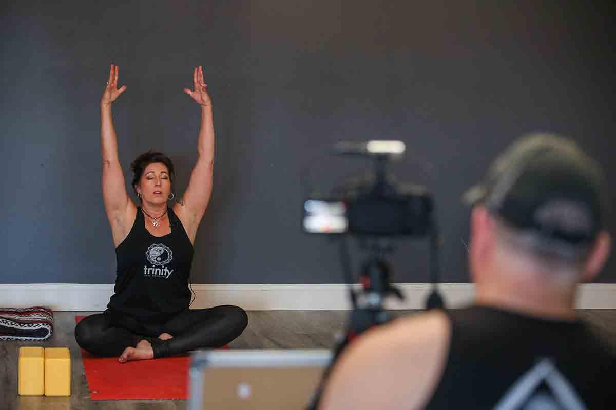 Janel Norton films a yoga class with her husband, Ray Norton. Chris Zuppa/The Penny Hoarder