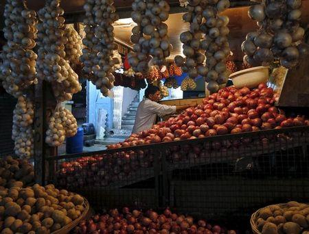 A customer buys onions from a stall at a local vegetable market in Mumbai
