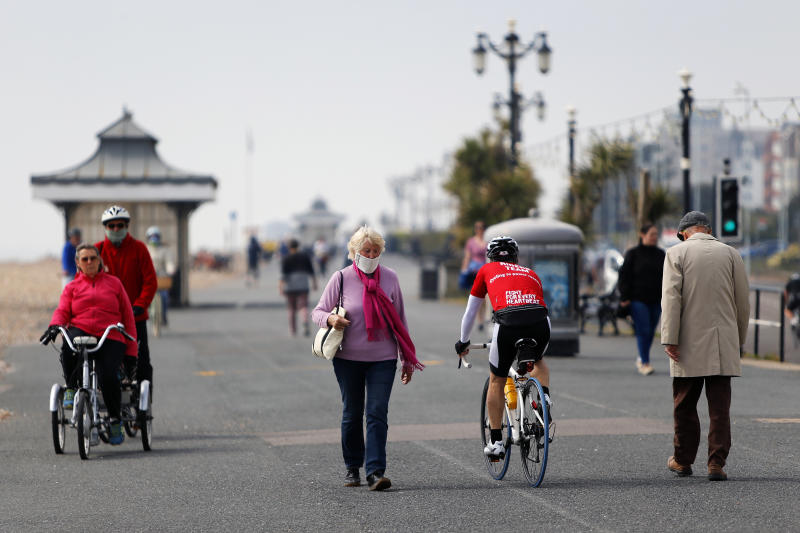 A woman in a protective mask walks past other people walking and cycling along Worthing promenade as the UK continues in lockdown to help curb the spread of the coronavirus.