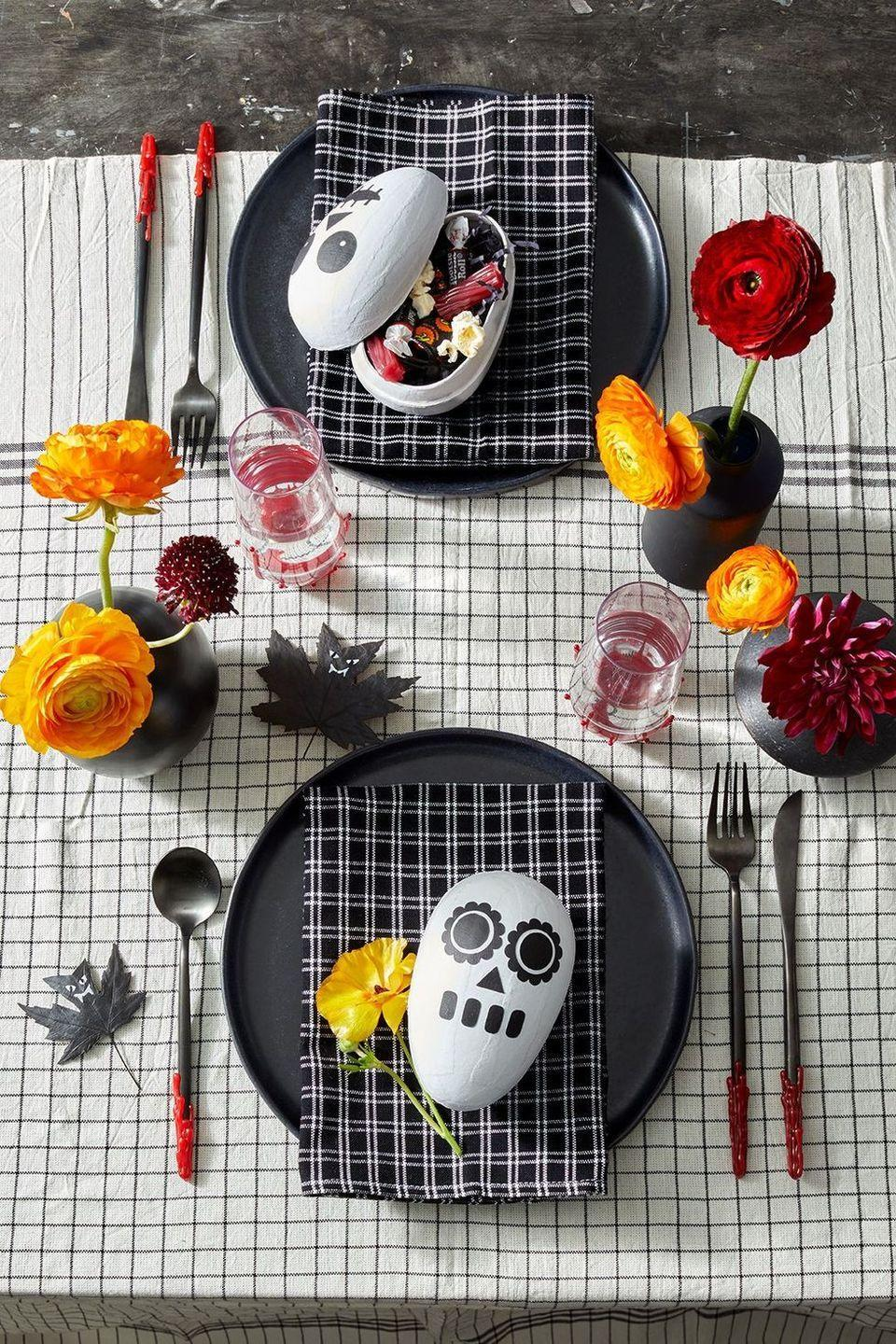"""<p>Once you create these little skull candy holders you can place one at each tablesetting as a sweet surprise for your guests. To make, spray paint all of the egg boxes white inside and out and let dry completely. Cut out the <a href=""""https://www.printables4mom.com/9-printable-skeleton-crafts/"""" rel=""""nofollow noopener"""" target=""""_blank"""" data-ylk=""""slk:skeleton face templates"""" class=""""link rapid-noclick-resp"""">skeleton face templates</a> out of black craft paper with scissors or a craft knife or make your own! Glue on the paper face pieces using a light layer of tacky glue and make sure you securely press down the pieces since the egg is round. </p>"""