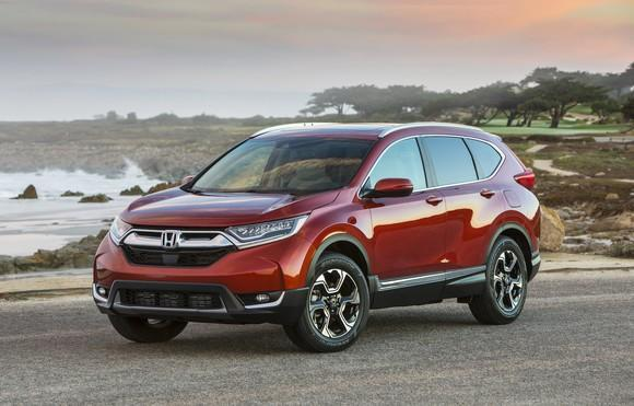 A red Honda CR-V, a compact crossover SUV, parked on a beach road.