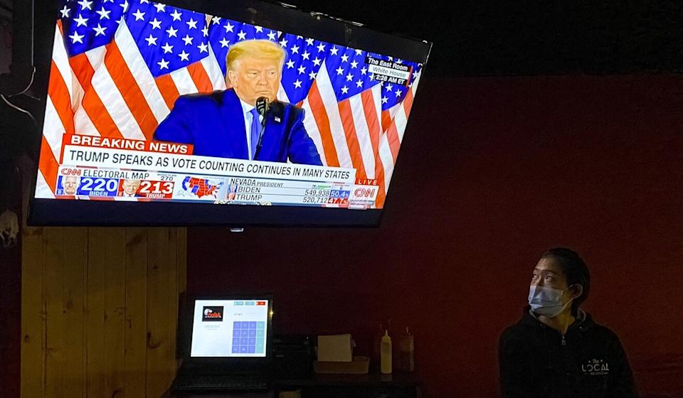 A restaurant worker watches Donald Trump give a speech on television. Photo: EPA-EFE