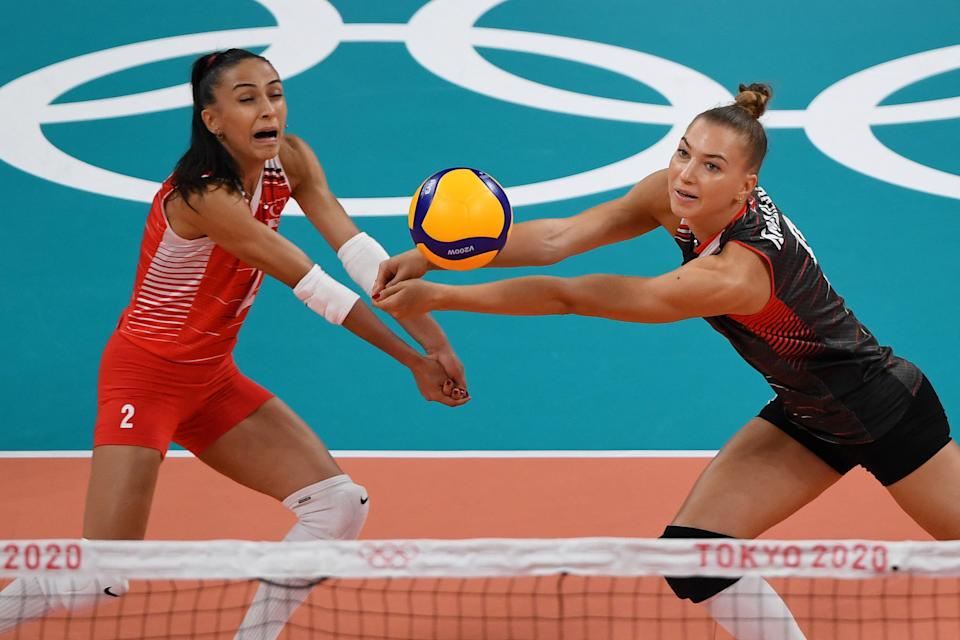 <p>Turkey's Meliha Ismailoglu (R) hits the ball in front of Cansu Ozbay in the women's preliminary round pool B volleyball match between Russia and Turkey during the Tokyo 2020 Olympic Games at Ariake Arena in Tokyo on August 2, 2021. (Photo by Yuri Cortez / AFP)</p>
