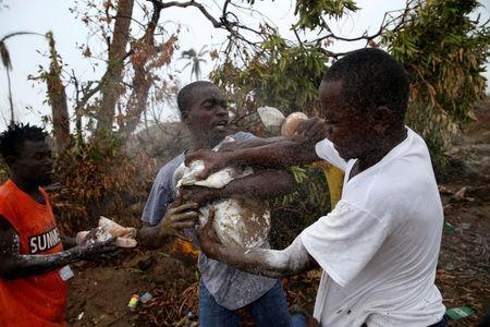 People fight while they assail a truck to try to get food after Hurricane Matthew hit Jeremie, Haiti, October 14, 2016. REUTERS/Carlos Garcia Rawlins/File Photo