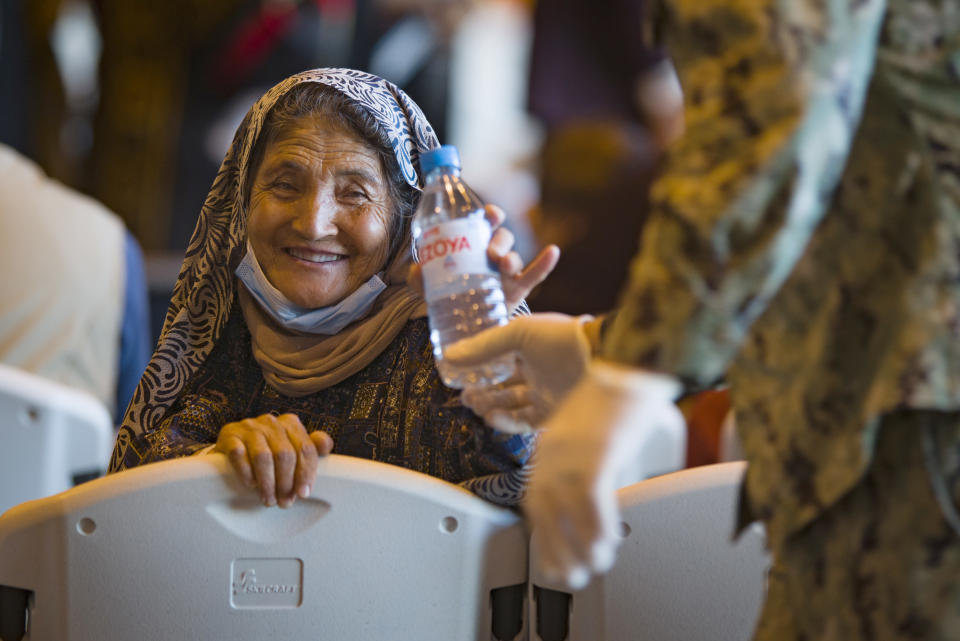 A woman from Afghanistan smiles after being given a bottle of water after disembarking from a U.S. airforce plane at the Naval Station in Rota, southern Spain, Tuesday Aug. 31, 2021. The United States completed its withdrawal from Afghanistan late Monday, ending America's longest war. (AP Photo/ Marcos Moreno)