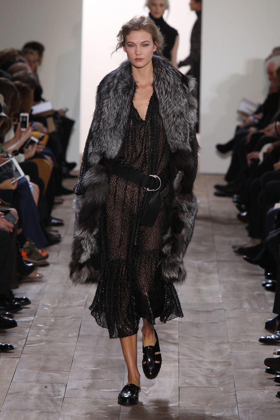 <p>Karlie Kloss walked the Michael Kors 2014 fall fashion show in a sheer dress, fur coat, and belt.</p>
