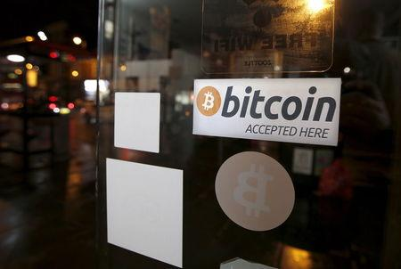 A bitcoin sticker is seen in the window of the 'Vape Lab' cafe, where it is possible to both use and purchase the bitcoin currency, in London