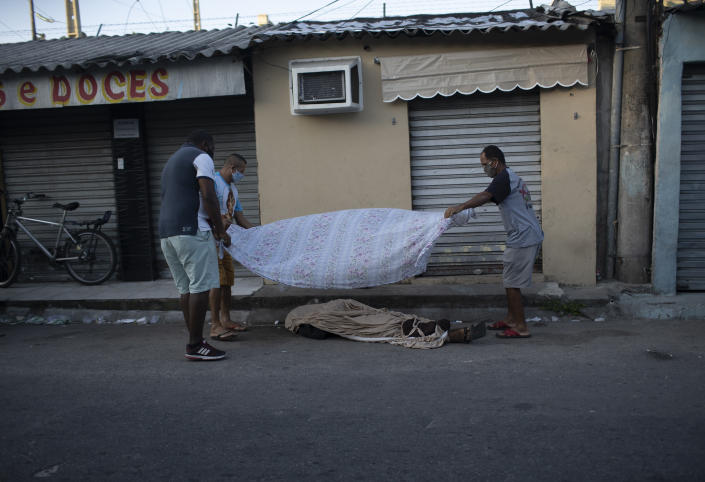 Neighbors cover the the body of Luiz Carlos Da Rocha, 36, with a sheet, as he lies on a street where he dropped dead at the Alemao Complex slum of Rio de Janeiro, Brazil, Tuesday, April 28, 2020. After more than 12 hours on the street the body of Da Rocha, who the family said suffered from epilepsy, had not been picked up by authorities. Military police said that due the new coronavirus pandemic, they only can remove corpses in cases of violent death. (AP Photo/Silvia Izquierdo)