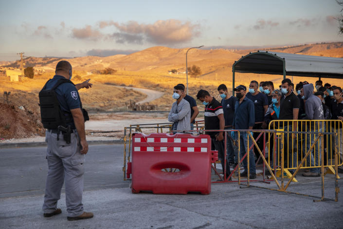"""FILE - In this Tuesday, June 30, 2020, file photo,Palestinian laborers line up to cross a checkpoint at the entrance to the Israeli settlement of Maale Adumim, near Jerusalem. Israel's premier human rights group has begun describing both Israel and its control of the Palestinian territories as a single """"apartheid"""" regime, using an explosive term that the Israeli government and its supporters vehemently reject. (AP Photo/Oded Balilty, File)"""