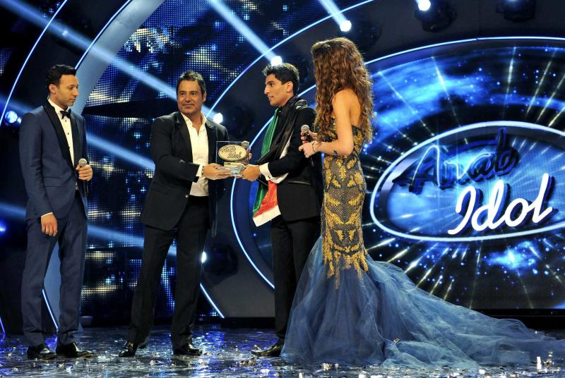In this Saturday, June 22, 2013 photo released by the MBC Group, singer Mohammed Assaf, second right, receives the Arab Idol award in Beirut, Lebanon. On Saturday night, Assaf became the first Palestinian to win the Arab world's version of American Idol, setting off wild celebrations across the Palestinian territories. After the victory, Palestinian President Mahmoud Abbas declared the singer an honorary ambassador. (AP Photo/MBC Group)
