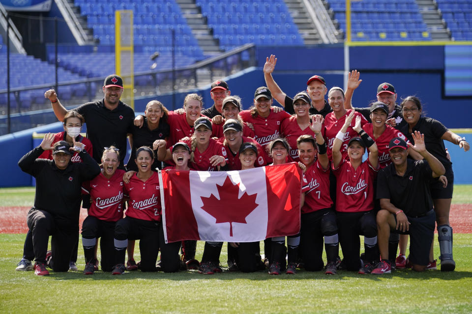 Members of team Canada pose for photographs after a softball game against Mexico at the 2020 Summer Olympics, Tuesday, July 27, 2021, in Yokohama, Japan. Canada won 3-2. (AP Photo/Sue Ogrocki)