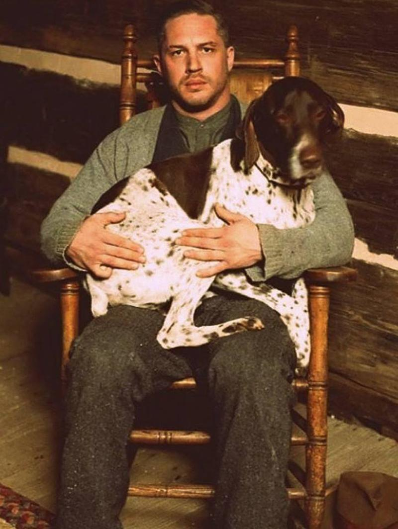 """<p>As much time as Tom spends with canines offscreen, he spends a lot of time in movies with them too. He cuddled up to this one in 2012's <em>Lawless</em>, even as he and one of his human co-stars, Shia LaBeouf, didn't quite hit it off. (Photo: <a rel=""""nofollow noopener"""" href=""""https://www.facebook.com/TomHardyUK/photos/a.573587869318913.136967.555896884421345/659986367345729/?type=3&theater"""" target=""""_blank"""" data-ylk=""""slk:Tom Hardy via Facebook"""" class=""""link rapid-noclick-resp"""">Tom Hardy via Facebook</a>)<br><br></p>"""