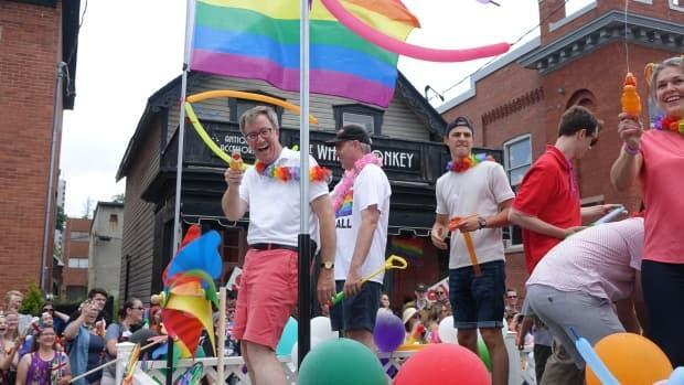 Watson, shown riding on the City of Ottawa's float at the 2018 Pride parade, officially came out as a gay man in August 2019.