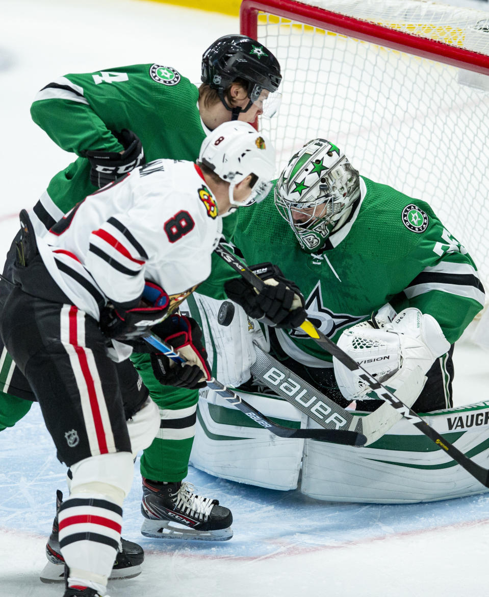 Chicago Blackhawks forward Dominik Kubalik (8) looks for the rebound as Dallas Stars defenseman Miro Heiskanen (4) and goaltender Anton Khudobin (35) defend during the first period of an NHL hockey game, Sunday, Feb. 23, 2020, in Dallas. Dallas won 2-1. (AP Photo/Brandon Wade)
