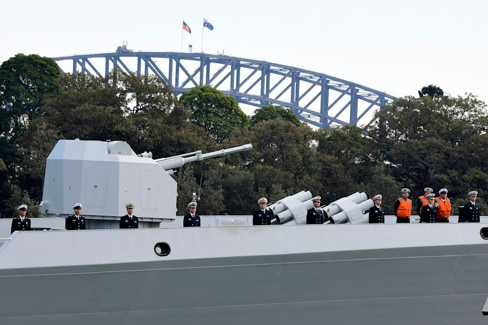 A gun onboard the Chinese vessel can be seen in front of the Sydney harbour bridge.