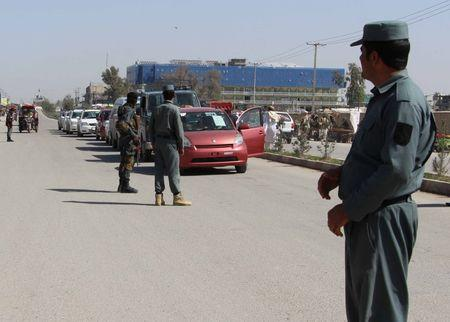 Afghan policemen inspect vehicles at a checkpoint in Helmand province