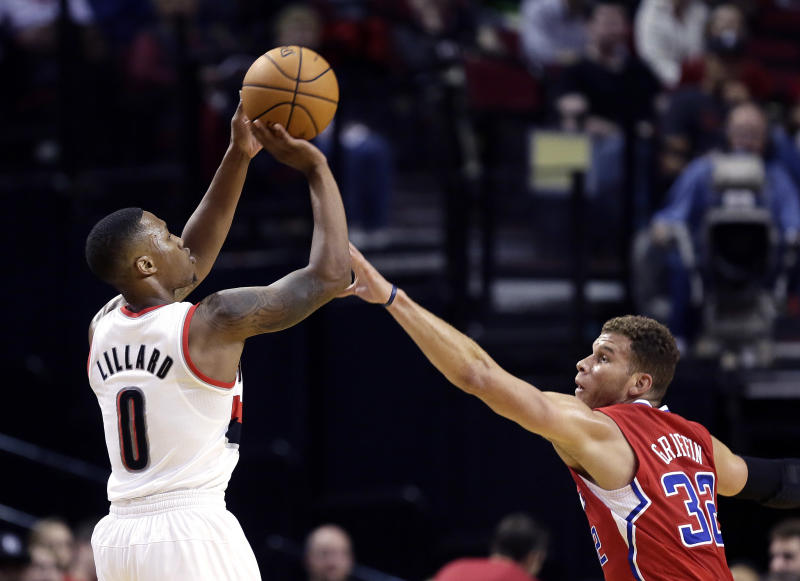 Portland Trail Blazers guard Damian Lillard, left, shoots over Los Angeles Clippers forward Blake Griffin during the first half of an NBA preseason basketball game in Portland, Ore., Monday, Oct. 7, 2013. (AP Photo/Don Ryan)