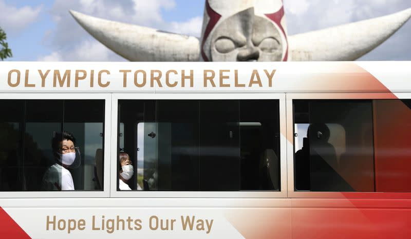 FILE PHOTO: Tokyo 2020 Olympic Torch Relay runners wearing protective masks wait inside a bus for their run at the Expo '70 Commemorative Park in Osaka