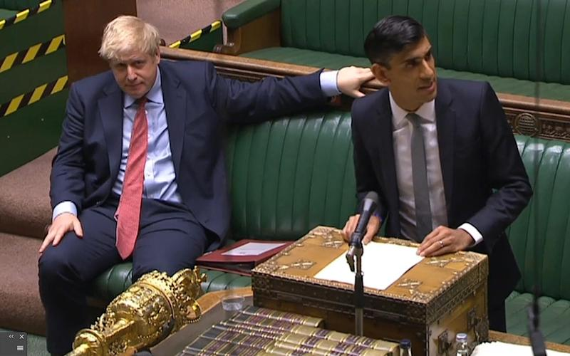 Prime Minister Boris Johnson watched on as Chancellor Rishi Sunak gave his 'mini-Budget' this afternoon - AFP