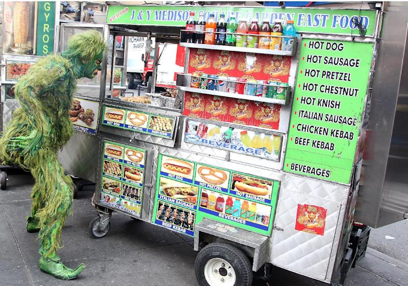 """In this Oct. 17, 2012 publicity image released by Madison Square Garden, Jeff McCarthy pretends to buy a hot dog while dressed as The Grinch in New York. McCarthy is the star of """"Dr. Seuss' How The Grinch Stole Christmas! The Musical"""" playing at Madison Square Garden this holiday season. (AP Photo/Madison Square Garden, Amanda Schwab/Starpix)"""
